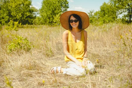 Photo for Attractive woman in sunglasses and straw hat sitting on dried grass in field - Royalty Free Image
