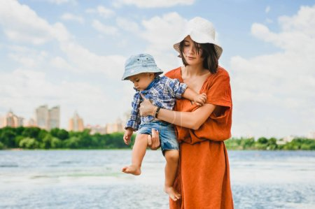 mother holding son near river in summer