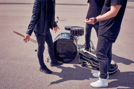 partial view of rock band in black clothing standing near musical instruments on street