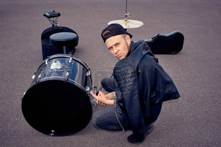 Drummer in black clothing pointing at drum kit on street