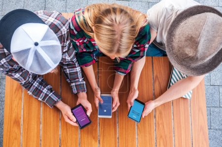 Photo for Overhead view of young friends using smartphones with social media apps - Royalty Free Image