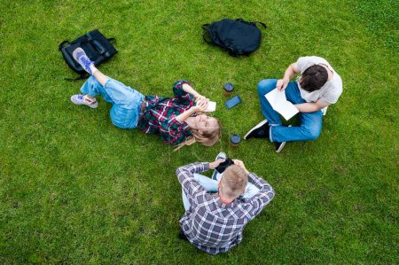top view of young friends reading book and using smartphones on green lawn