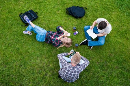 overhead view of young friends reading book and using smartphones on green grass
