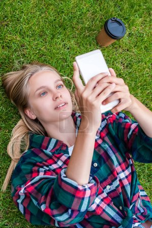 Photo for High angle view of beautiful blonde girl lying on grass and using smartphone - Royalty Free Image