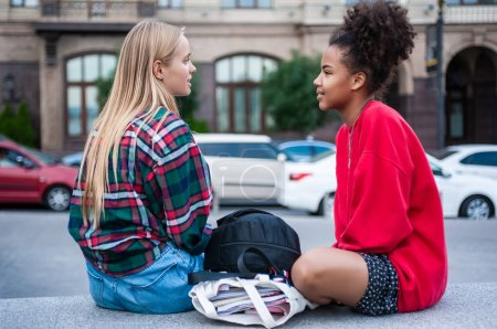 side view of two multiethnic girls sitting and looking at each other on street