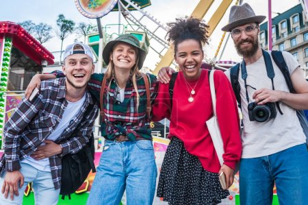Photo for Cheerful young multiethnic friends standing together and smiling at camera in amusement park - Royalty Free Image