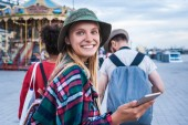 beautiful young woman holding smartphone and smiling at camera while spending time with friends in amusement park