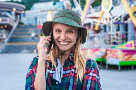 cheerful young woman talking by smartphone and smiling at camera in amusement park