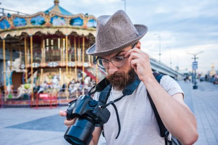 bearded young man in hat and eyeglasses using digital camera in amusement park