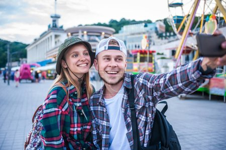 happy young couple taking selfie with smartphone in amusement park