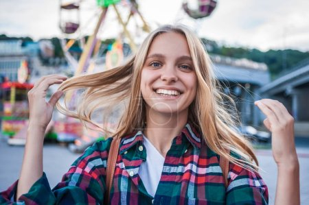 happy blonde girl smiling at camera while spending time in amusement park