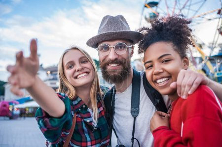 Photo for Cheerful young multiethnic friends smiling at camera in amusement park - Royalty Free Image