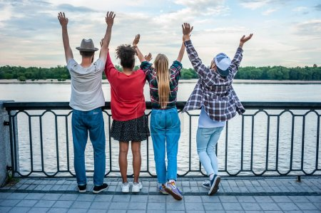 back view of four multiethnic friends raising hands at riverbank