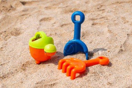 Photo pour Cuillère en plastique, râteau et arrosoir pour jouer sur la plage - image libre de droit