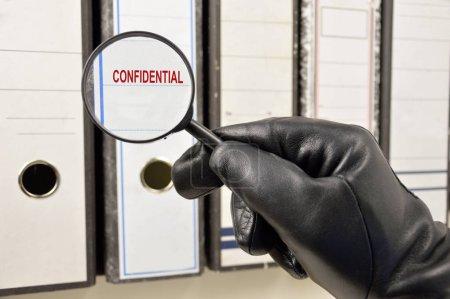 Photo pour Voleur avec loupe à la recherche de fichiers confidentiels au bureau - image libre de droit