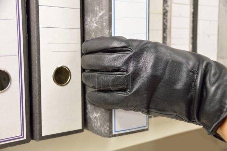 Photo pour Voleur qui vole un classeur à anneaux et des fichiers confidentiels dans un bureau - image libre de droit