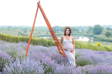 Photo for Attractive pregnant woman in straw hat leaning on wooden ladder at lavender field and touching belly - Royalty Free Image