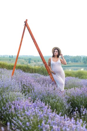 Photo for Beautiful pregnant woman in white dress leaning on wooden ladder at lavender field and touching belly - Royalty Free Image
