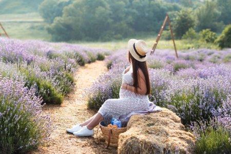 side view of pregnant woman sitting on hay bale in violet lavender field