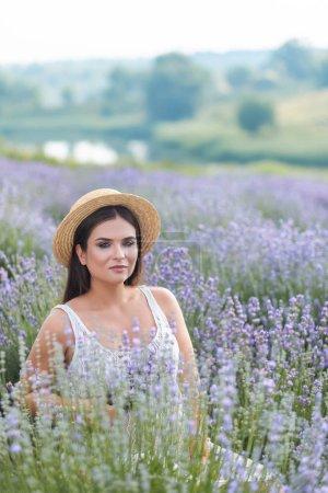 Foto de Mujer atractiva en sombrero de paja en campo lila violeta - Imagen libre de derechos