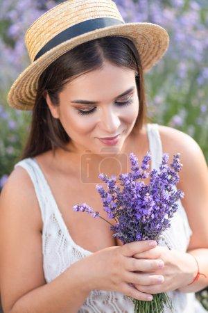 Foto de Retrato de hermosa mujer en vestido blanco oliendo flores de lavanda en campo - Imagen libre de derechos