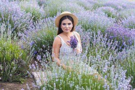 Photo pour Belle femme en robe blanche assise dans un champ de lavande violette et tenant un petit bouquet - image libre de droit