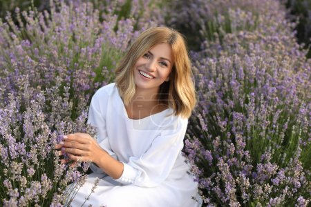 Photo for Smiling attractive woman in white dress sitting in violet lavender field and looking at camera - Royalty Free Image