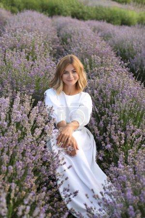 Photo pour Jolie femme en robe blanche assis au champ lavande violette et regardant la caméra - image libre de droit