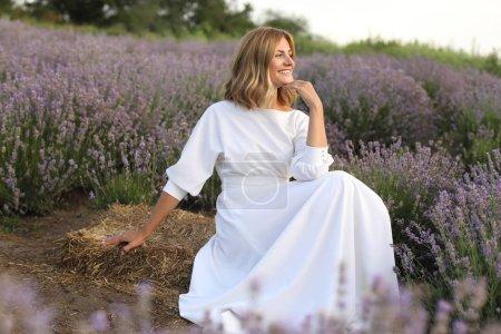 Photo pour Vue latérale d'une jolie femme en robe blanche assis dans champ lavande violette et à la recherche de suite - image libre de droit