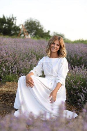 Photo pour Belle femme souriante dans une robe blanche assis au champ lavande violette - image libre de droit