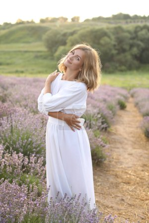 smiling attractive woman in white dress hugging herself in violet lavender field