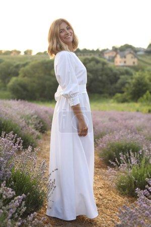 Photo pour Jolie femme en robe blanche, debout dans le champ lavande violette et regardant la caméra de sourire - image libre de droit