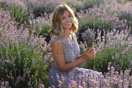 Photo pour Jolie femme tenant fleurs champ de lavande violette et regardant la caméra de sourire - image libre de droit
