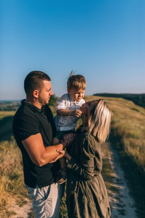Photo for Happy young parent carrying adorable little son while standing on rural path - Royalty Free Image