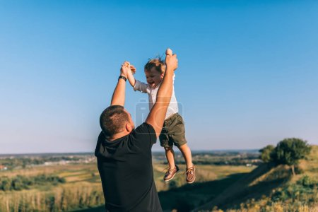 young father playing and having fun with happy little son outdoors