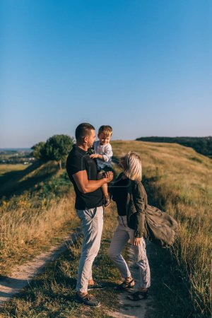 Photo for Smiling young parents looking at adorable little son while standing on rural trail - Royalty Free Image