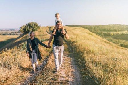 Foto de Felices padres jóvenes cogidos de la mano al padre llevando a adorable hijito en cuello - Imagen libre de derechos