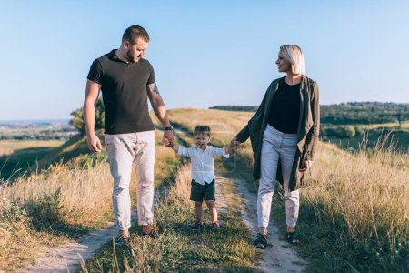 happy parents with adorable little son holding hands and walking on rural trail