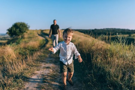 adorable happy little boy running on rural path while father walking behind