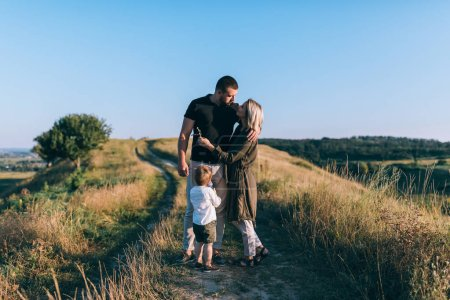 happy parents with cute little son standing together on rural trail