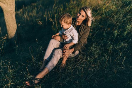 Photo for Happy young mother looking at camera while sitting with cute little son on green grass - Royalty Free Image