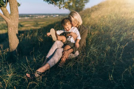 Photo for Smiling young mother and cute little son sitting together on green grass at sunset - Royalty Free Image