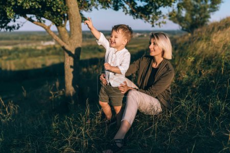 happy young mother sitting on grass and looking at cute little son pointing with finger outdoors