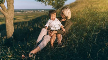 happy young mother and cute little son sitting together on green grass at sunset