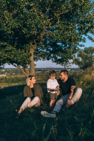 happy family with one child resting together on green grass