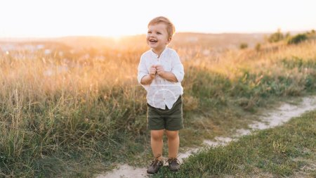 Photo for Adorable happy child laughing while standing on rural path at sunset - Royalty Free Image