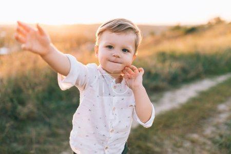 Photo pour Adorable petit enfant souriant à la caméra tout en marchant à l'extérieur au coucher du soleil - image libre de droit