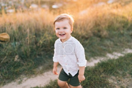 Photo for High angle view of adorable little boy walking in rural trail and smiling at camera at sunset - Royalty Free Image
