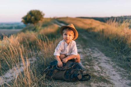 Photo for Adorable little boy with bag sitting on rural path and looking at camera - Royalty Free Image
