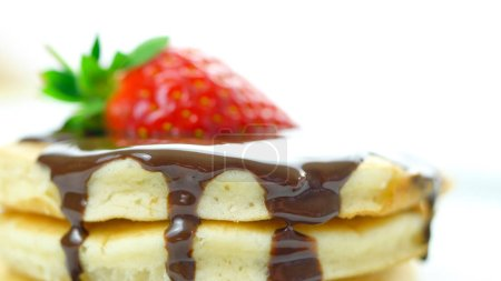 Stack of pancakes with strawberry and drizzled wit...